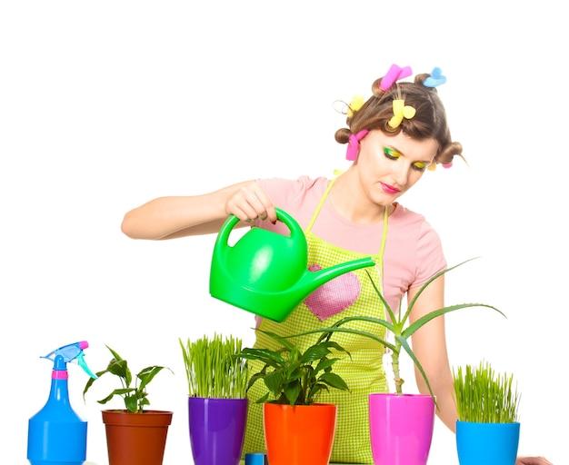Belle jeune femme au foyer, arrosage des plantes dans des pots de fleurs isolés sur blanc