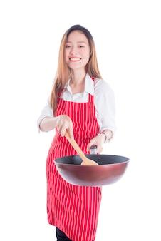 Belle jeune femme au foyer asiatique portant tablier rouge et tenant la casserole avec le sourire
