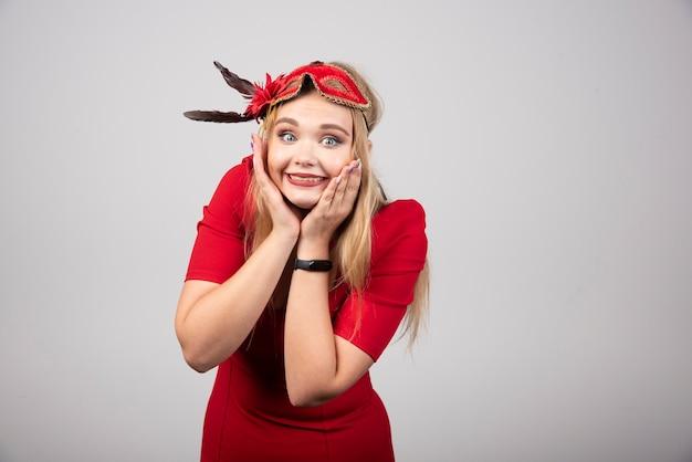 Belle jeune femme au masque rouge tenant son visage.