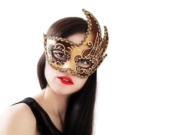 Belle jeune femme au masque vénitien doré isolé sur blanc