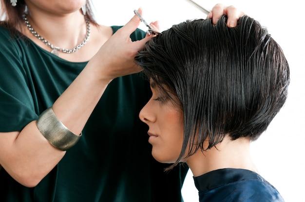 Belle jeune femme au salon de coiffure