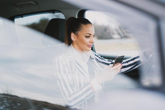 Belle jeune femme au volant et envoyer des sms dans la ville.