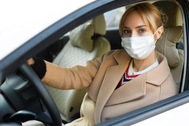 Belle jeune femme au volant d'une voiture portant un masque médical