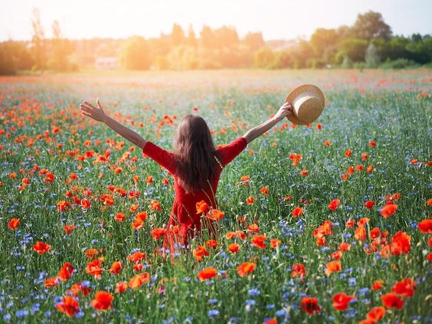 Belle jeune femme aux bras levés dans un champ de coquelicot