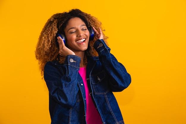 Belle jeune femme aux cheveux afro écoutant de la musique avec le casque souriant.