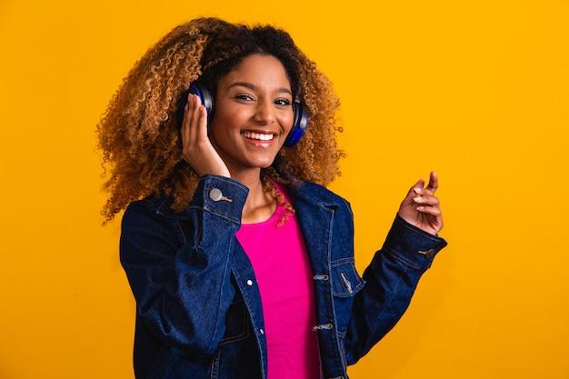 Belle jeune femme aux cheveux afro écoutant de la musique avec son casque sur fond jaune avec un espace libre pour le texte.