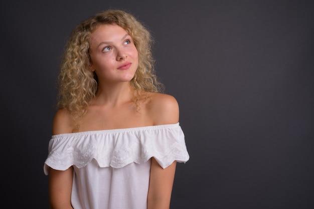 Belle jeune femme aux cheveux blonds bouclés contre gris