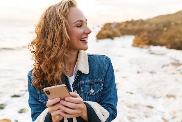 Belle jeune femme aux cheveux blonds bouclés utilisant un smartphone en marchant au bord de la mer