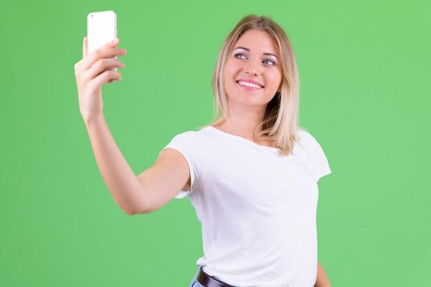 Belle jeune femme aux cheveux blonds contre la chrominance sur vert