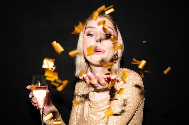 Belle jeune femme aux cheveux blonds avec flûte de champagne soufflant des confettis dorés de sa main tout en profitant de la fête