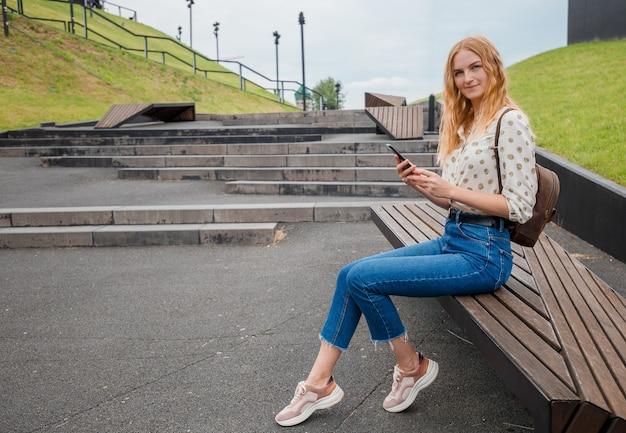 Belle jeune femme aux cheveux blonds, messagerie sur le smartphone dans la rue de la ville. fille de taper des sms au téléphone dans la rue dans une journée ensoleillée.