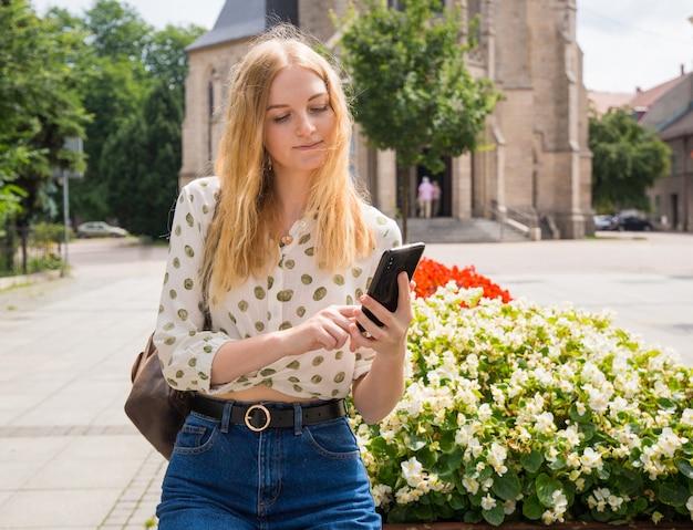 Belle jeune femme aux cheveux blonds, messagerie sur le smartphone de la ville