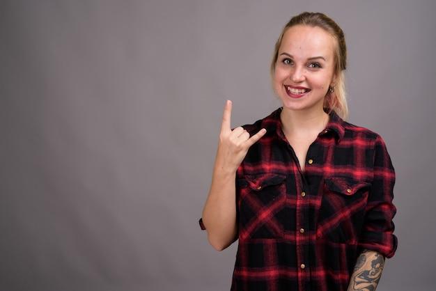Belle jeune femme aux cheveux blonds portant une chemise à carreaux rouge sur fond gris