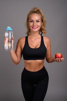 Belle jeune femme aux cheveux blonds prêt pour la gym contre le gris