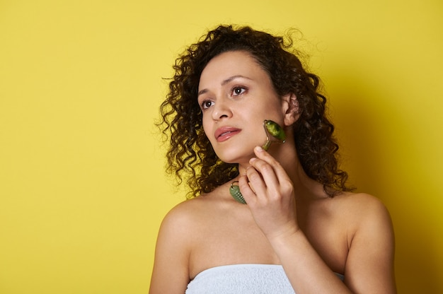 Belle jeune femme aux cheveux bouclés à l'aide d'un rouleau de jade pour le massage du visage et les soins de la peau. tourné avec une ombre douce sur jaune, le tout avec un espace de copie.