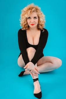 Belle jeune femme aux cheveux bouclés blonde posant en robe noire