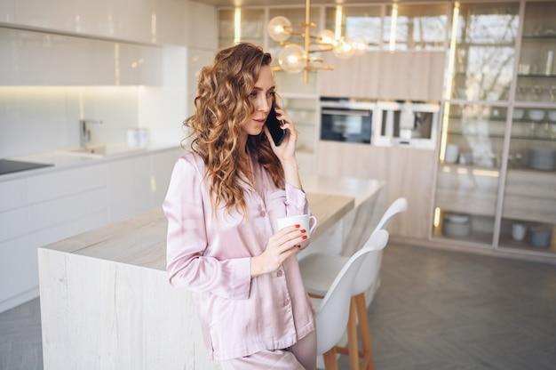 Belle jeune femme aux cheveux bouclés, boire du café à la maison le matin de week-end paresseux en pyjama rose confortable.