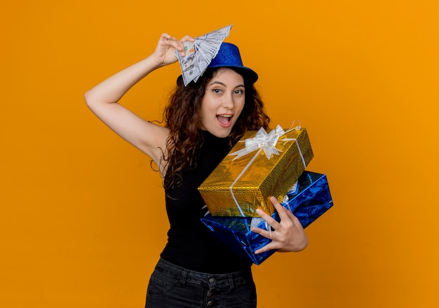 Belle jeune femme aux cheveux bouclés en chapeau de fête tenant de l'argent et des cadeaux à la recherche de canera heureux et excité debout sur un mur orange