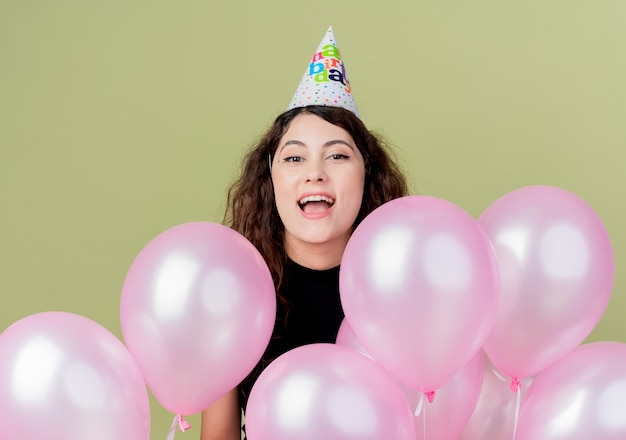 Belle jeune femme aux cheveux bouclés dans un chapeau de vacances avec des ballons à air heureux et excité célébrant la fête d'anniversaire debout sur un mur léger