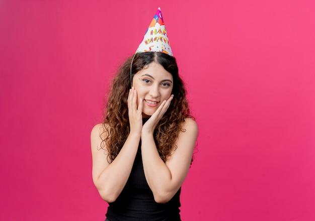Belle jeune femme aux cheveux bouclés dans un chapeau de vacances heureux et surpris tenant le visage avec le concept de fête d'anniversaire bras debout sur le mur rose