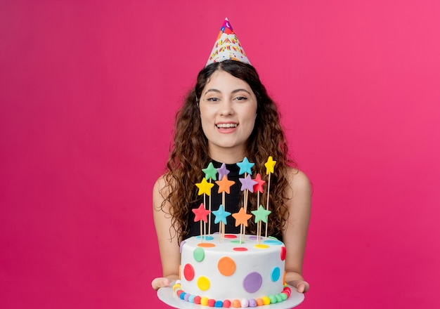 Belle jeune femme aux cheveux bouclés dans un chapeau de vacances holding birthday cake hapy et joyeux anniversaire concept de fête sur rose