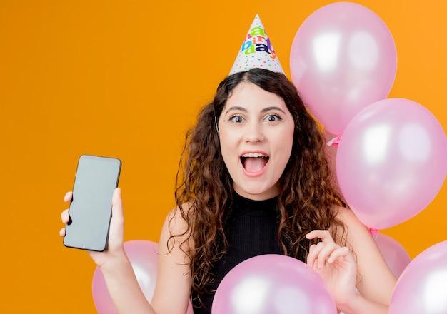 Belle jeune femme aux cheveux bouclés dans un chapeau de vacances montrant le concept de fête d'anniversaire heureux nad smartphone heureux debout avec des ballons à air sur mur orange