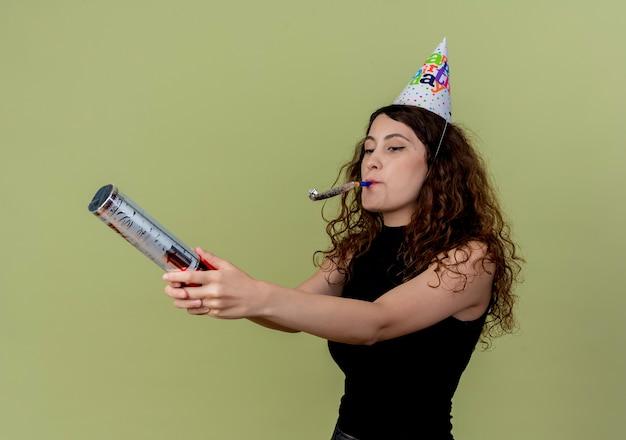 Belle jeune femme aux cheveux bouclés dans un chapeau de vacances soufflant sifflet célébrant la fête d'anniversaire sur la lumière