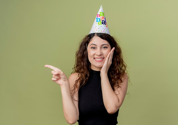 Belle jeune femme aux cheveux bouclés dans un chapeau de vacances souriant joyeusement pointant avec le doigt sur le côté concept de fête d'anniversaire debout sur un mur léger
