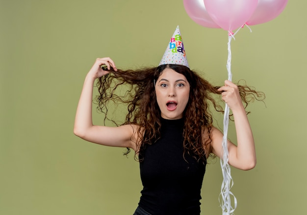 Belle jeune femme aux cheveux bouclés dans un chapeau de vacances tenant des ballons à air confus et surpris concept de fête d'anniversaire debout sur un mur léger