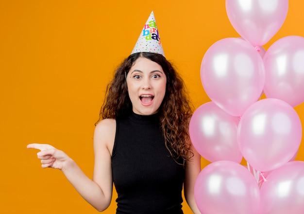 Belle jeune femme aux cheveux bouclés dans un chapeau de vacances tenant des ballons à air heureux et excité pointant avec le doigt sur le côté concept de fête d'anniversaire debout sur le mur orange