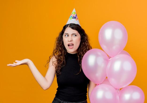 Belle jeune femme aux cheveux bouclés dans un chapeau de vacances tenant des ballons à air à la notion de fête d'anniversaire confus debout sur un mur orange