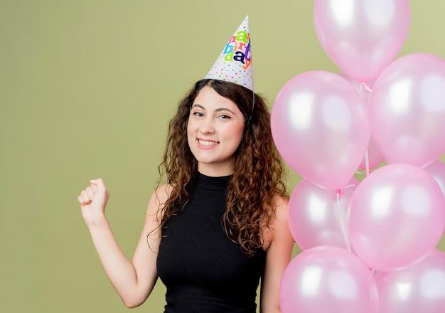 Belle jeune femme aux cheveux bouclés dans un chapeau de vacances tenant des ballons à air serrant le poing heureux et excité concept de fête d'anniversaire debout sur un mur léger