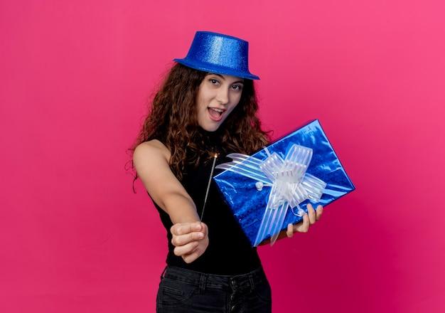 Belle jeune femme aux cheveux bouclés dans un chapeau de vacances tenant boîte-cadeau d'anniversaire et sparkler joyeux et joyeux souriant joyeusement concept de fête d'anniversaire debout sur le mur rose
