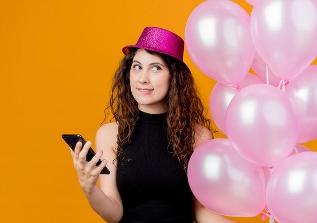 Belle jeune femme aux cheveux bouclés dans un chapeau de vacances tenant bouquet de ballons à air et smartphone regardant la pensée mordre les lèvres anniversaire concept de fête debout sur le mur orange