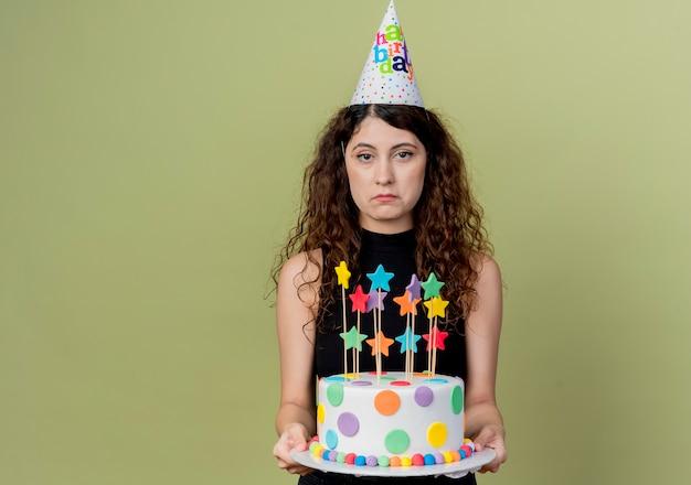 Belle jeune femme aux cheveux bouclés dans un chapeau de vacances tenant un gâteau d'anniversaire avec une expression triste sur le visage debout sur un mur léger