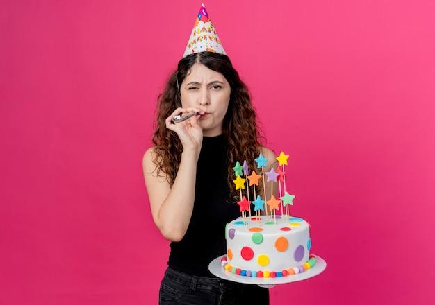 Belle jeune femme aux cheveux bouclés dans un chapeau de vacances tenant le gâteau d'anniversaire soufflant sifflet heureux et positif fête d'anniversaire concept debout sur le mur rose