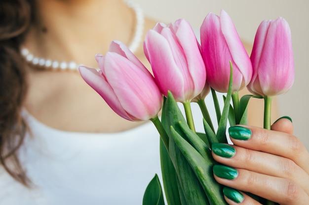 Belle jeune femme aux cheveux bouclés dans une robe blanche avec un collier tenant une tulipe rose