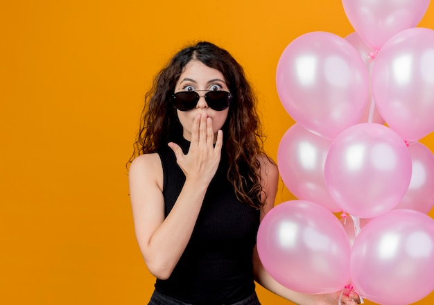 Belle jeune femme aux cheveux bouclés dans des verres noirs tenant un bouquet de ballons à air surpris et étonné debout sur un mur orange