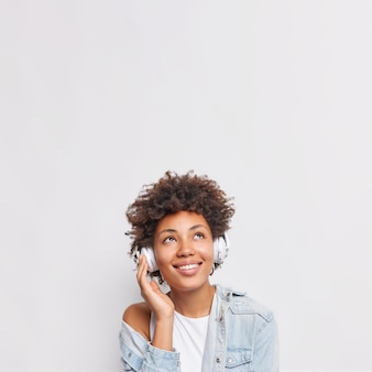 Belle jeune femme aux cheveux bouclés a une expression rêveuse gaie sourit agréablement écoute de la musique via des écouteurs porte des poses de chemise en jean contre un mur blanc