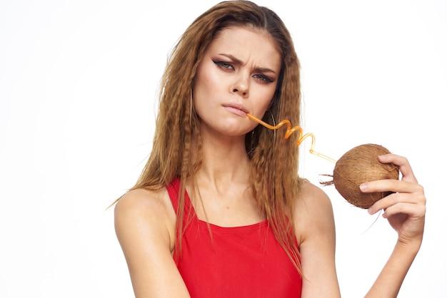 Belle jeune femme aux cheveux bouclés en maillot de bain boit un cocktail de noix de coco, tropiques