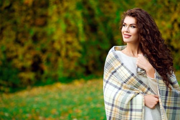 Belle jeune femme aux cheveux bouclés marchant à l'automne dans le parc et enveloppée dans une couverture