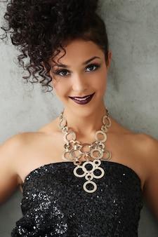 Belle jeune femme aux cheveux bouclés noirs et robe brillante noire