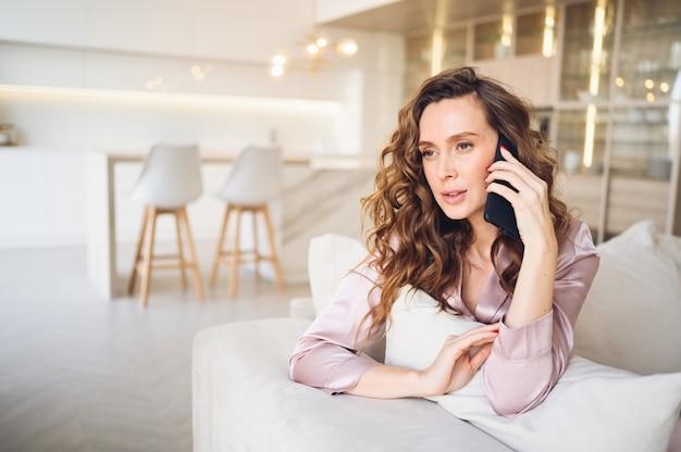 Belle jeune femme aux cheveux bouclés en pyjama rose au canapé blanc le matin. dame parlant téléphone à l'intérieur du salon de style scandinave.