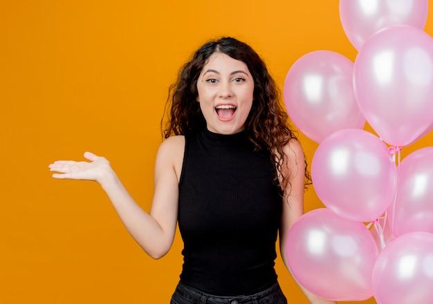 Belle jeune femme aux cheveux bouclés tenant bouquet de ballons à air heureux et excité concept de fête d'anniversaire debout sur le mur orange