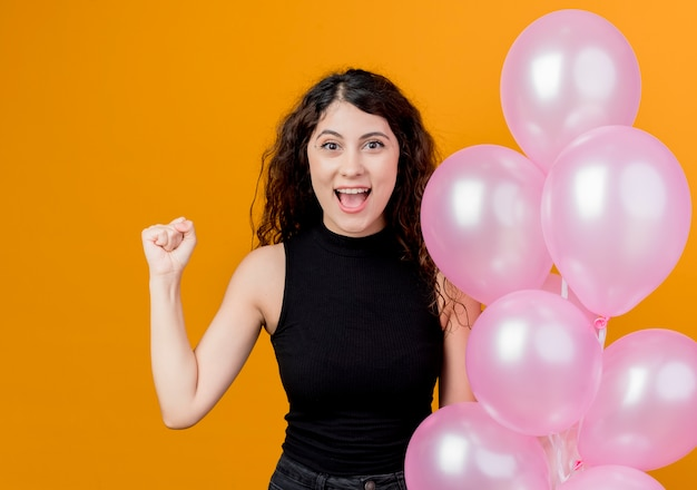 Belle jeune femme aux cheveux bouclés tenant bouquet de ballons à air serrant le poing heureux et excité concept de fête d'anniversaire debout sur le mur orange