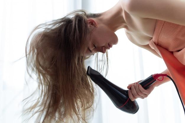 Belle jeune femme aux cheveux bruns dans une serviette de bain utilise un sèche-cheveux pour sécher ses longs cheveux après la douche dans la chambre. soin des cheveux.