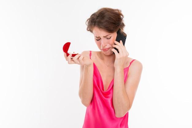Belle jeune femme aux cheveux bruns ondulés, peau propre, dents plates, beau sourire, en jersey rose, tenant une boîte de bague d'entraînement, parlant au téléphone et bouleversé