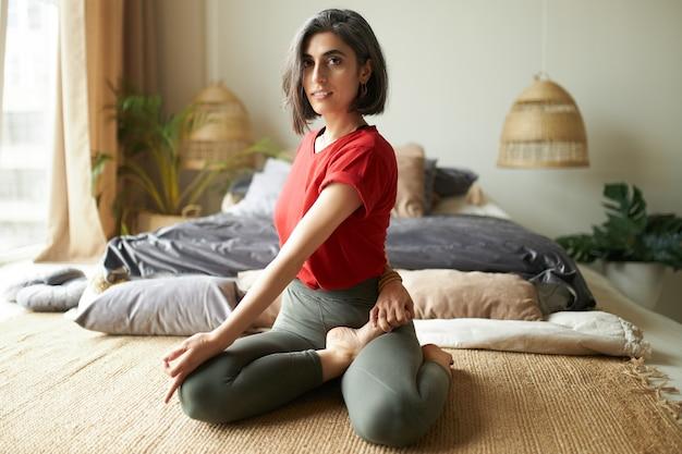 Belle jeune femme aux cheveux gris en vêtements de sport assis en demi-seigneur des poissons posture ou ardha matsyendrasana