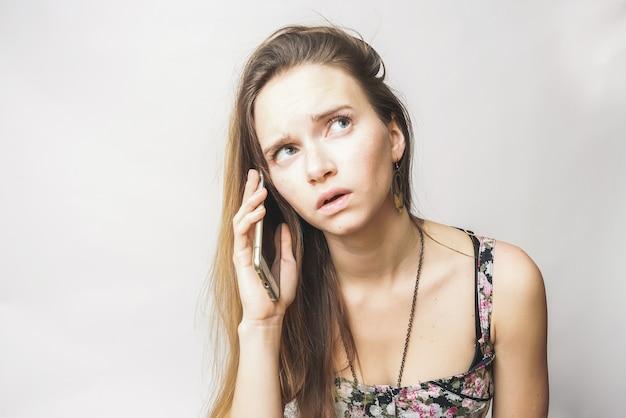 Belle jeune femme aux cheveux longs, aux yeux bleus, bouleversée, parlant au téléphone avec surprise. cherche quelque part