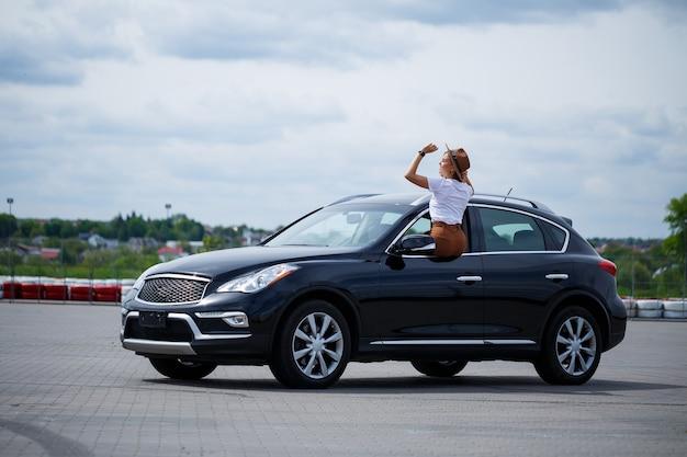 Belle jeune femme aux cheveux longs est assise dans une voiture noire sur un parking. jolie fille en vêtements décontractés. voyage en voiture